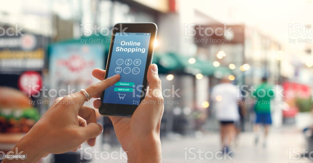 Man hands using smartphone for online shopping on street at city background.  E-commerce icon network on screen. Digital marketing and Mobile payments. Online shopping concepts - foto stock