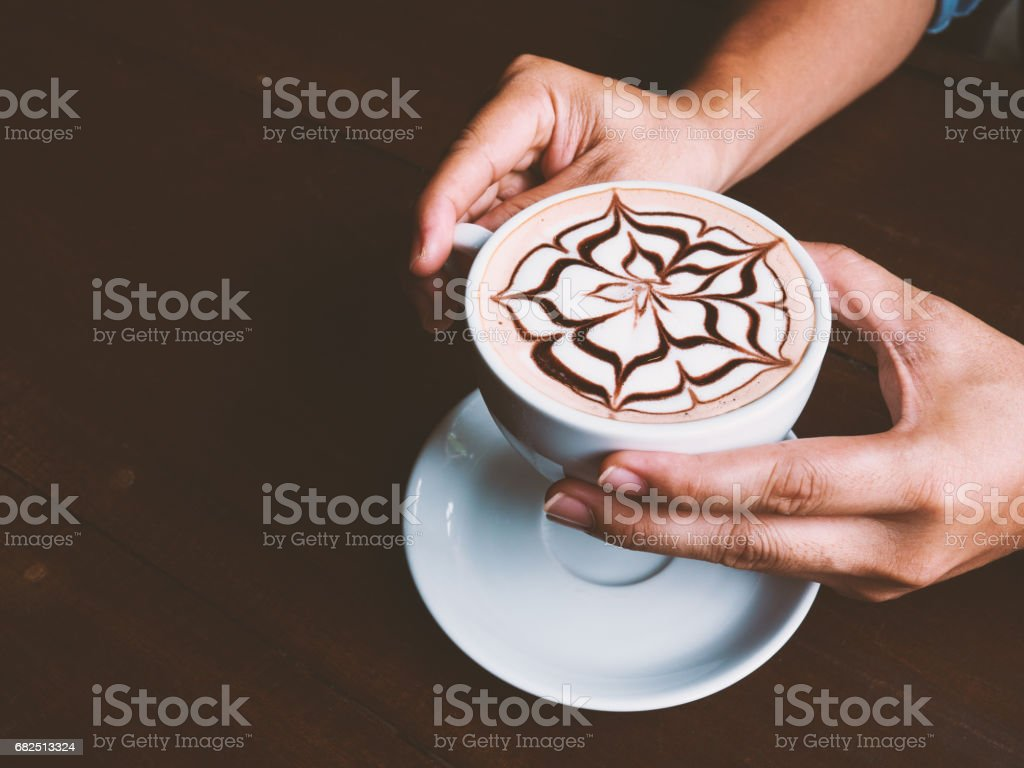 Man hands with coffee cup of latte art on wooden table at cafe. Selective focus and vintage tone. Copy space. royalty-free stock photo