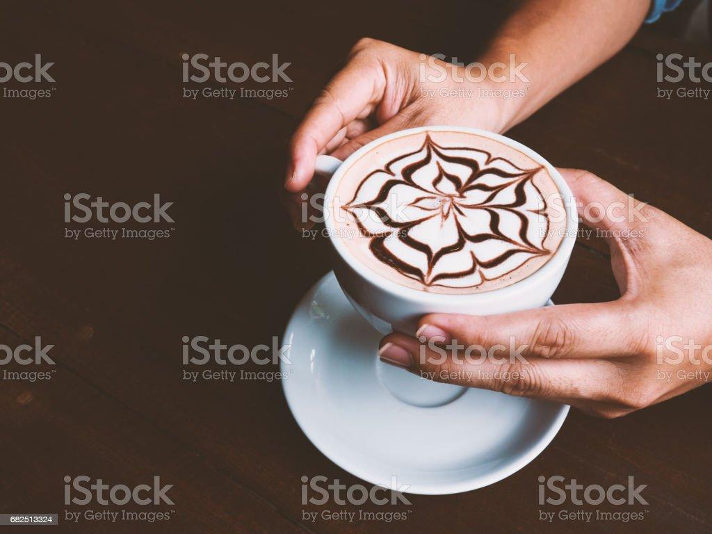 Hombre de las manos con la taza de café del arte del latte en la mesa de madera en café. Enfoque selectivo y tono vintage. Copia espacio. foto de stock libre de derechos