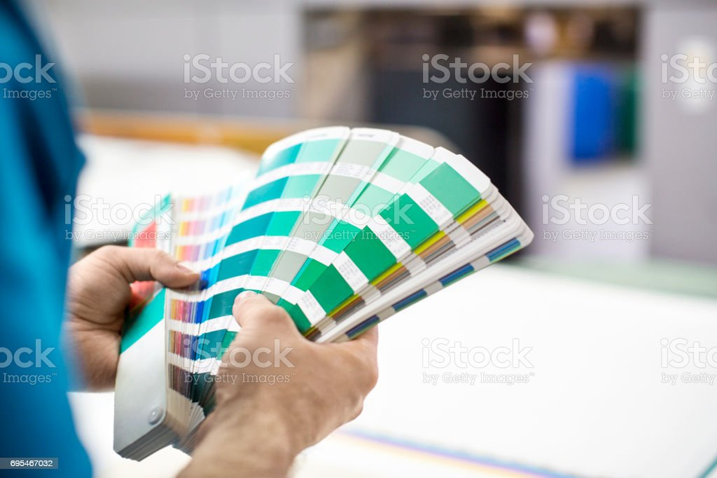 Man hands with colour samples at printing press stock photo