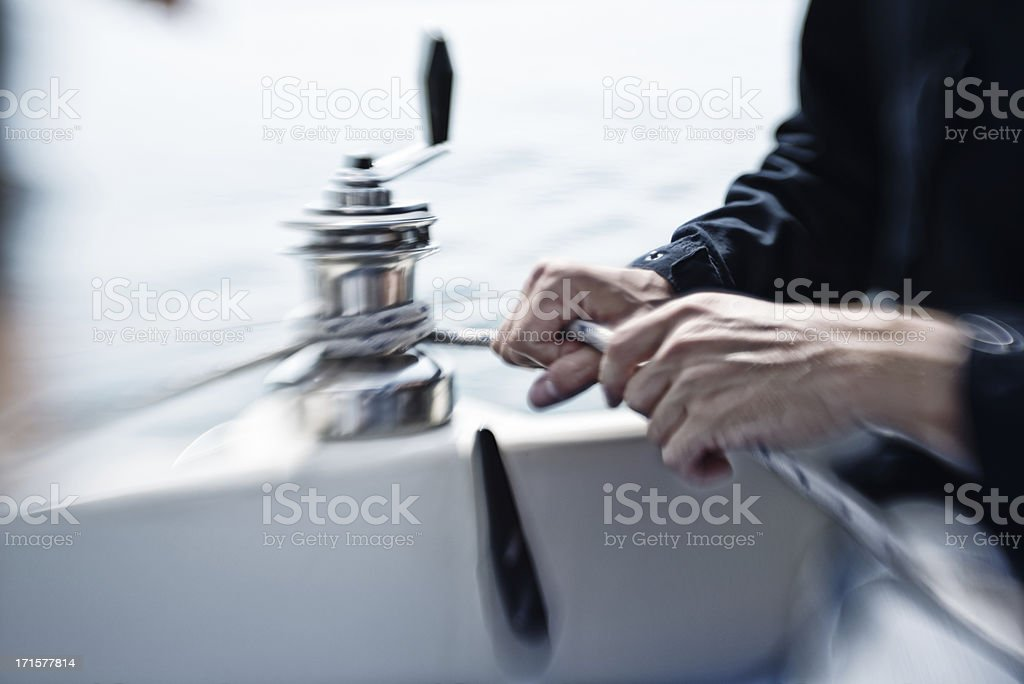man hands working on a winch during sailturn stock photo