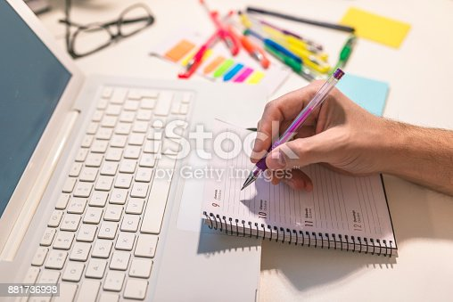 istock Man hands writing notes in daily planner. 881736998