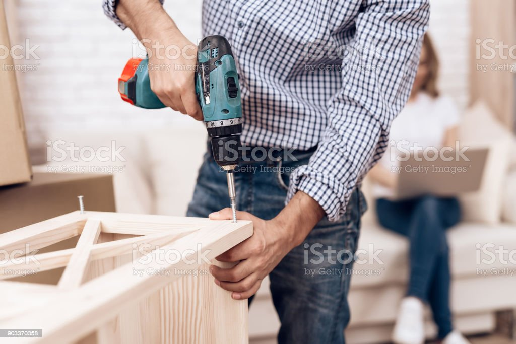 Man handyman is engaged in assembly of furniture. Repairman is engaged in repairing furniture. stock photo