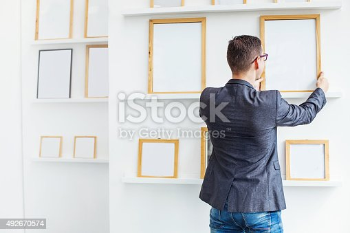 istock man hanging a blank poster in exhibition hall 492670574