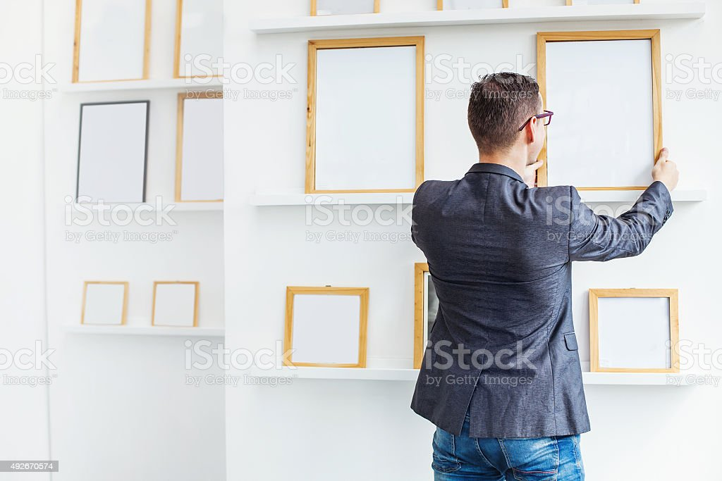 man hanging a blank poster in exhibition hall stock photo
