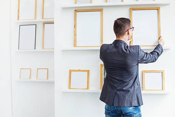 mann hängen eine leere poster im exhibition hall - karten wandkunst stock-fotos und bilder