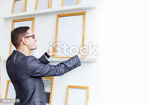 896826068 istock photo man hanging a blank poster in exhibition hall 492670678
