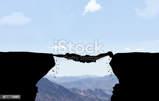 Man hanging between two rocks in front of mountain background.