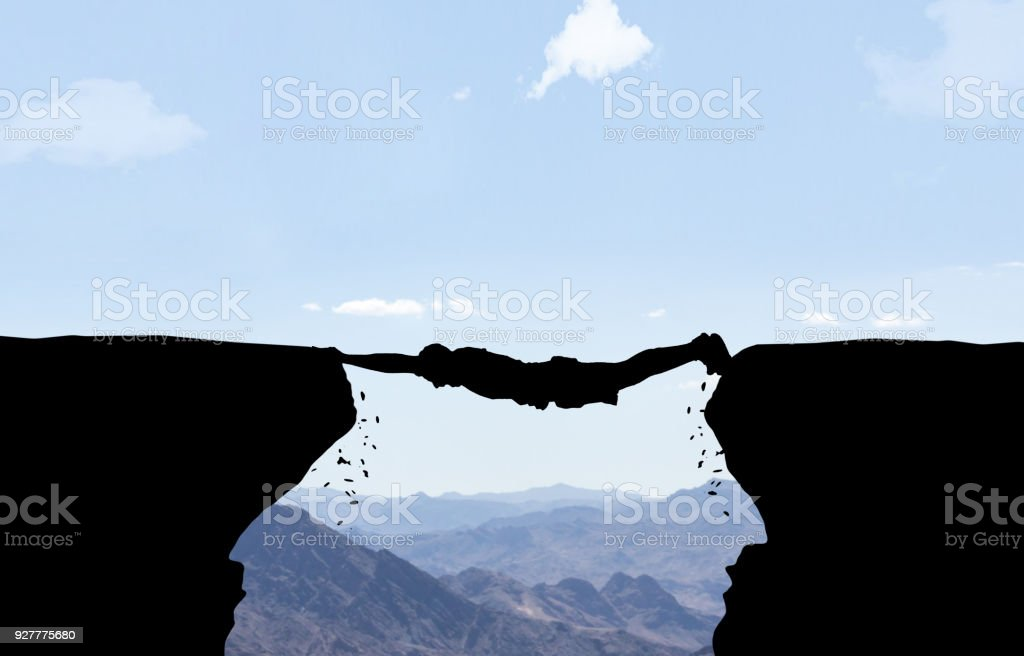 Man hanging between two rocks. stock photo