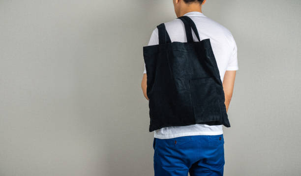 Man hanging black tote bag in the back stock photo