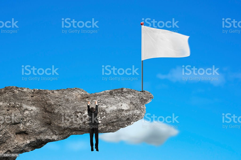 man hanging on cliff with blank white flag and sky stock photo