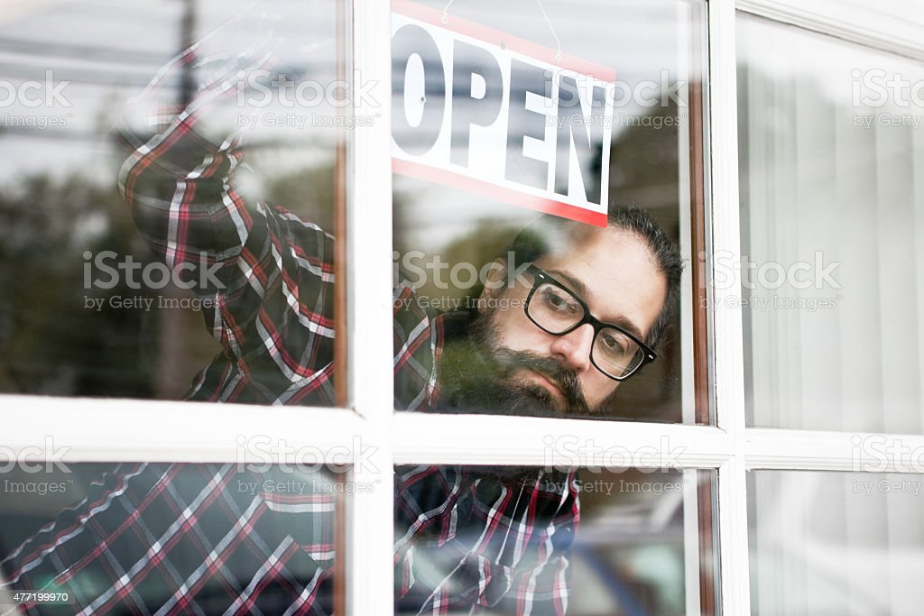 Man Hanging Open Sign On Window Looking For Customers stock photo