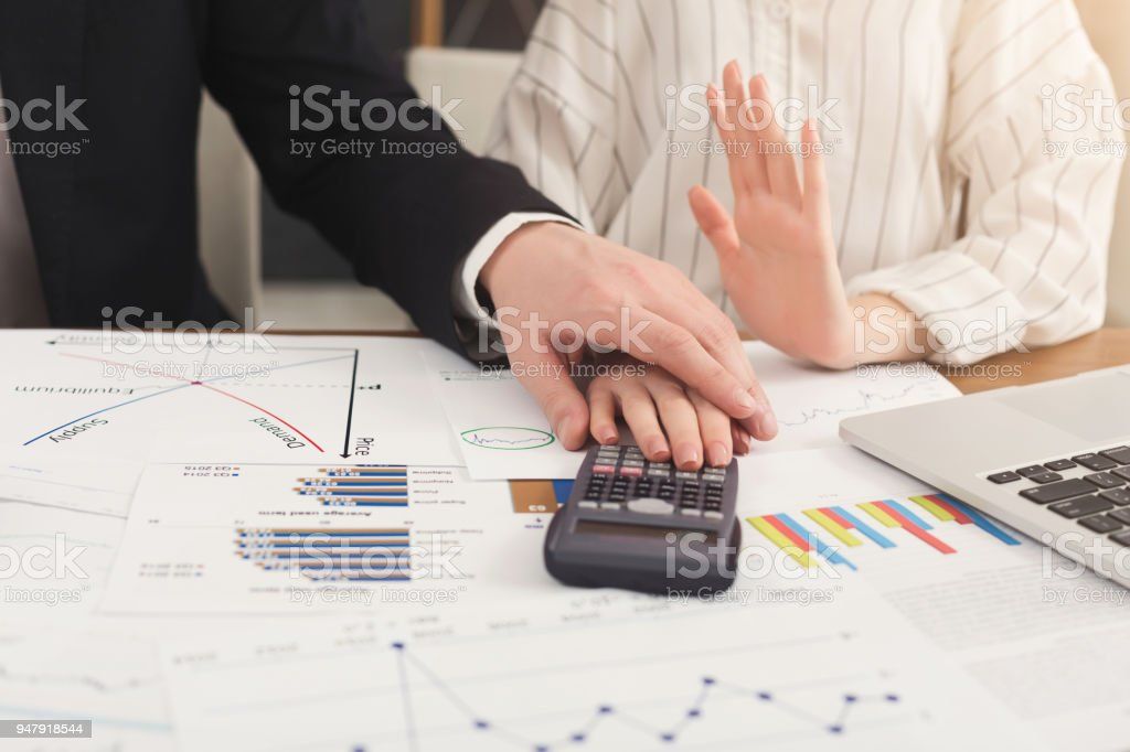 Man harassing his female colleague at work stock photo
