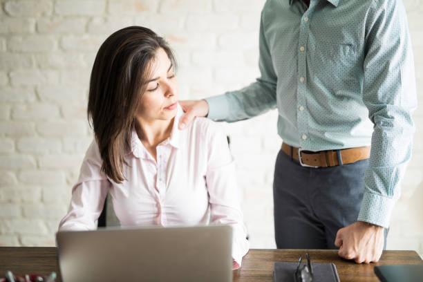 Man harrasing a woman at work Abusive boss harassing a female colleague in the office while she looks uncomfortable and upset harassment stock pictures, royalty-free photos & images