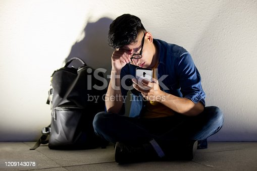 asian man is upset about cyber bullying and sit outdoor in the evening