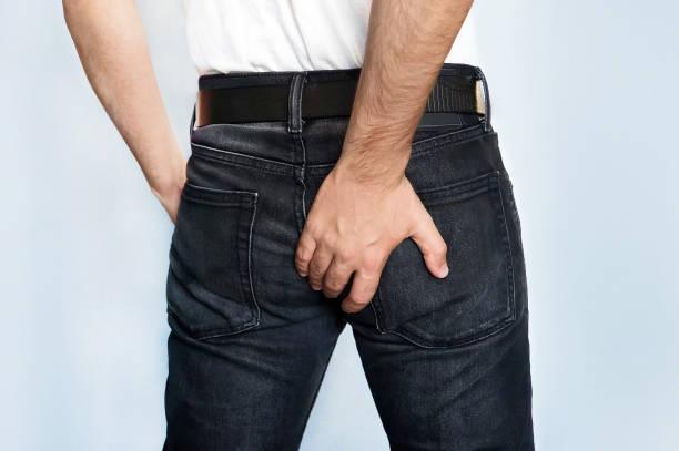 mann hält seine po ist diarrhö - tantra massage stock-fotos und bilder