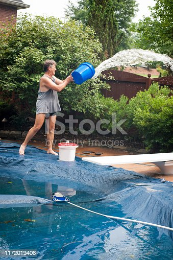 Adult Caucasian man in  his 50's wearing swimming trunks and a tank tshirt hauls buckets of water from a flooded pool cover on an inground swimming pool after a pump failure and  torrential rain storm, Indiana, USA