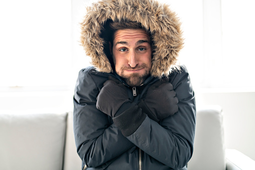 Man have cold on the sofa at home with winter coat