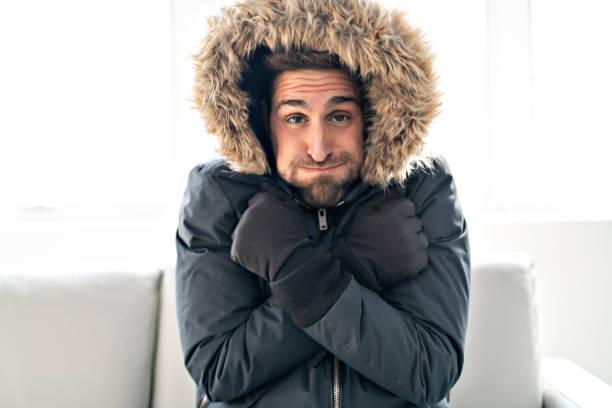 一個男人穿著冬衣在家裡的沙發上感冒了 - 寒冷的 個照片及圖片檔