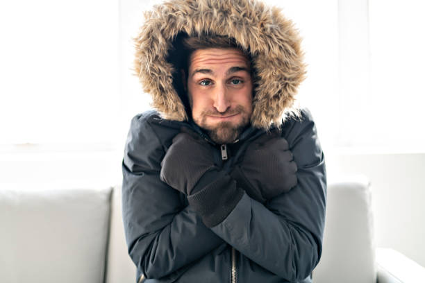 A Man have cold on the sofa at home with winter coat Man have cold on the sofa at home with winter coat warm clothing stock pictures, royalty-free photos & images