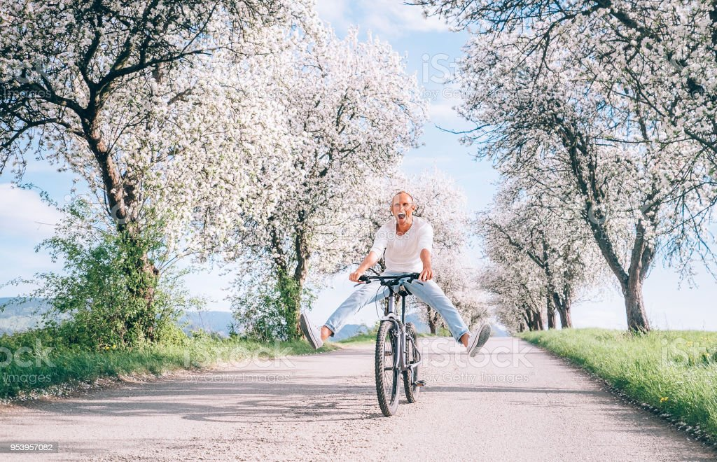 Man have fun when rides a bicycle on country road stock photo