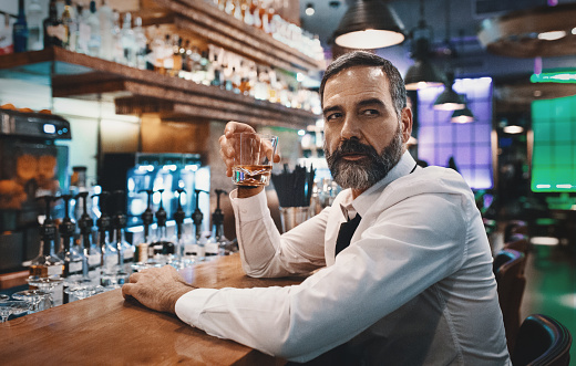 istock Man having a drink in a bar. 878545516