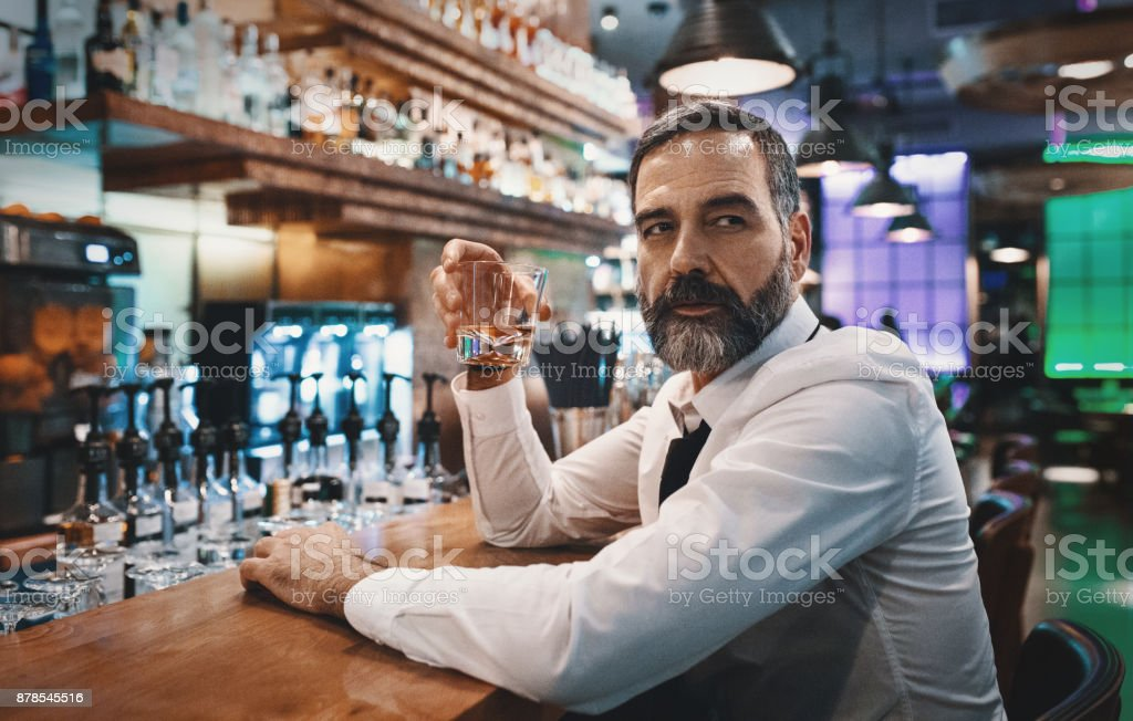 Man having a drink in a bar. stock photo