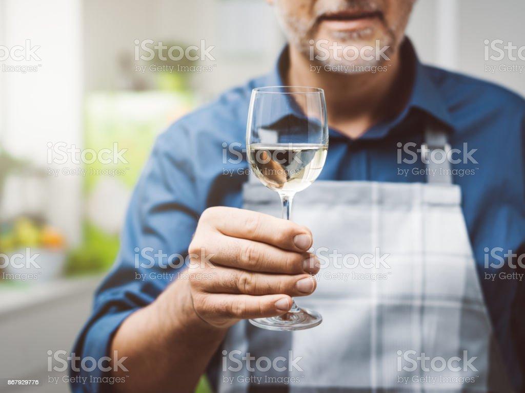 Homem tomando uma taça de vinho na cozinha - foto de acervo