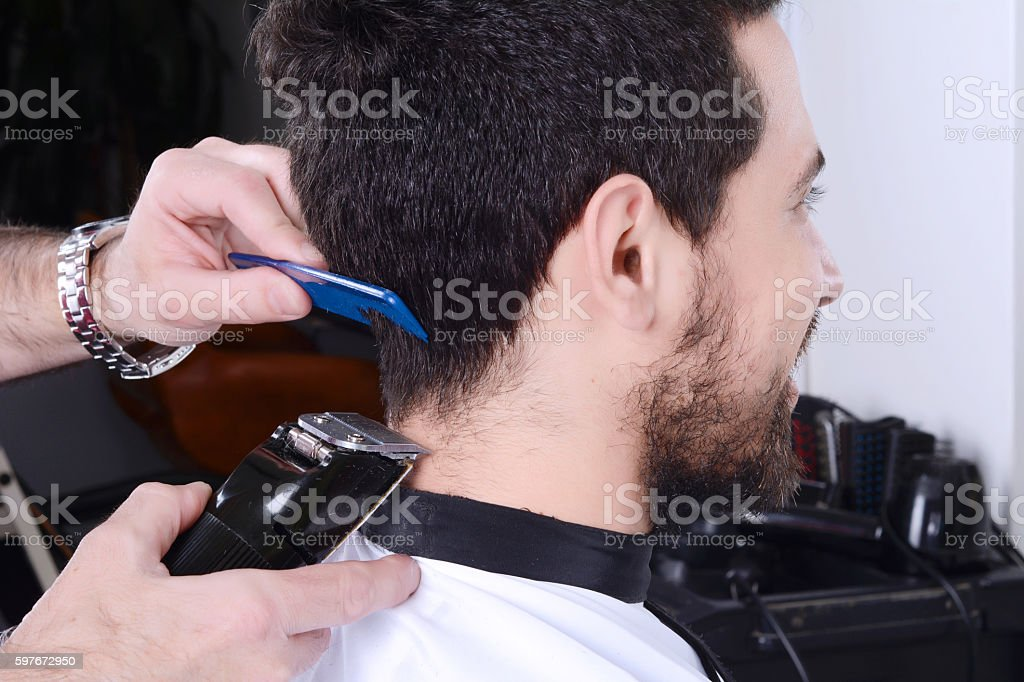 Man having a haircut with hair clippers. stock photo