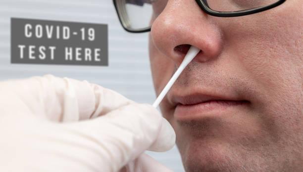 Man having a Nasal Swab test for Coronavirus with sign stock photo