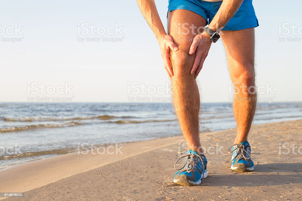 Man having a pain in his knee stock photo
