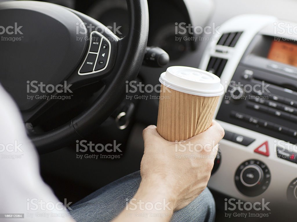 Man having a to-go cup of coffee while driving stock photo