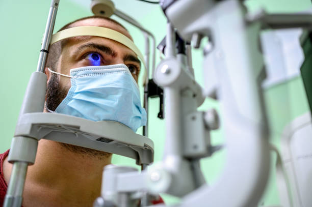 Man having an eye exam at ophthalmologist's office Male ophthalmologist examining young man's eyesight with optical instrument. Male ophthalmologist measuring an eyesight of a young man with diagnostic medical tool. eye doctor mask stock pictures, royalty-free photos & images