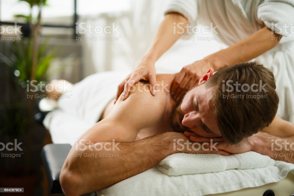 Man having back massage at the health spa. stock photo