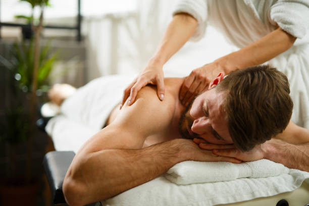 man having back massage at the health spa. - massaggio foto e immagini stock