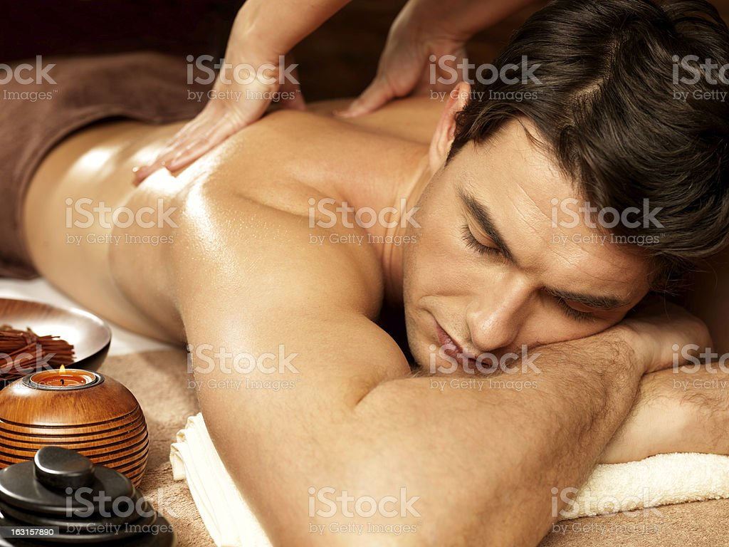 Man having back massage in the spa salon stock photo