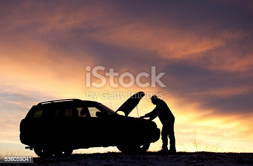 A silhouette of a man beside his vehicle having mechanical difficulty. SUV. Roadside assistance needed. Car trouble. Horizontal colour image. Rural highway.