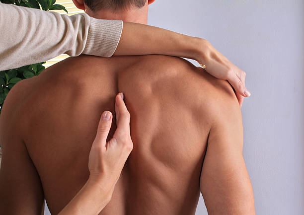 man having chiropractic back adjustment close up. - chiropractic care stock photos and pictures