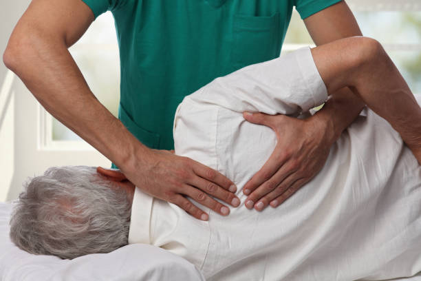 man having chiropractic back adjustment. osteopathy, alternative medicine, pain relief concept. physiotherapy, sport injury rehabilitation - chiropractic care stock photos and pictures