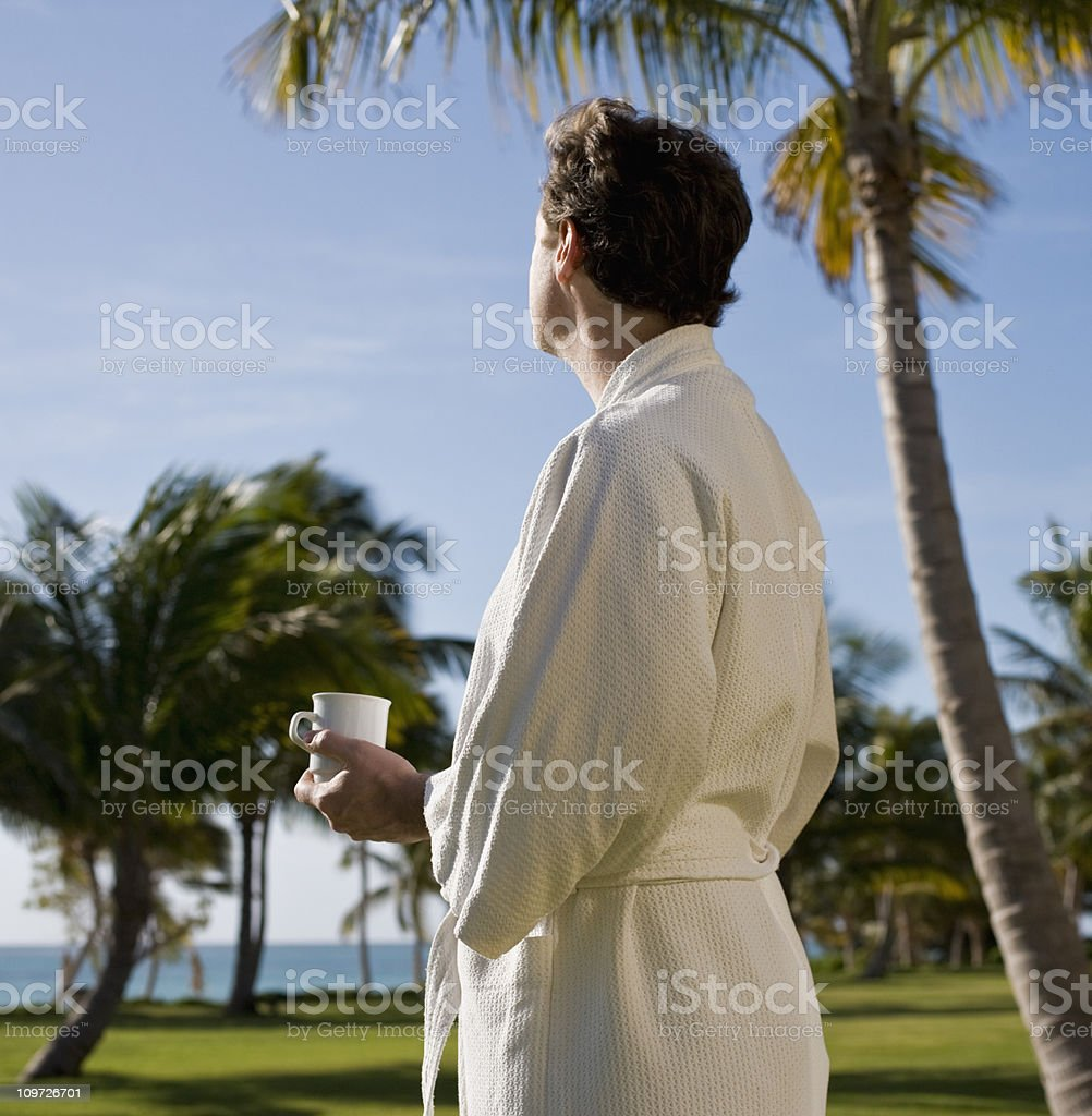 Man Having Coffee Outside Under Palm Trees royalty-free stock photo