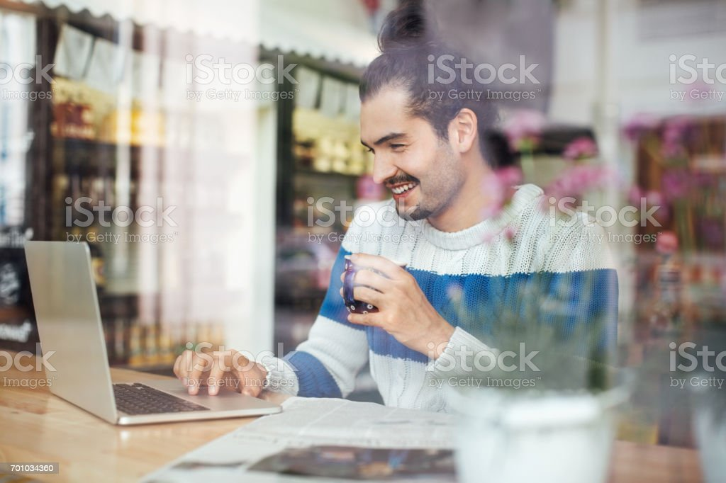 Man having coffee while using laptop in cafe stock photo