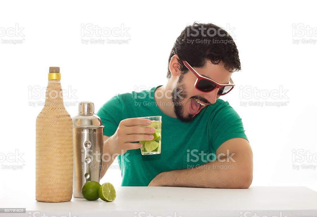 Man having fun at a bar table, drinking a cocktail stock photo