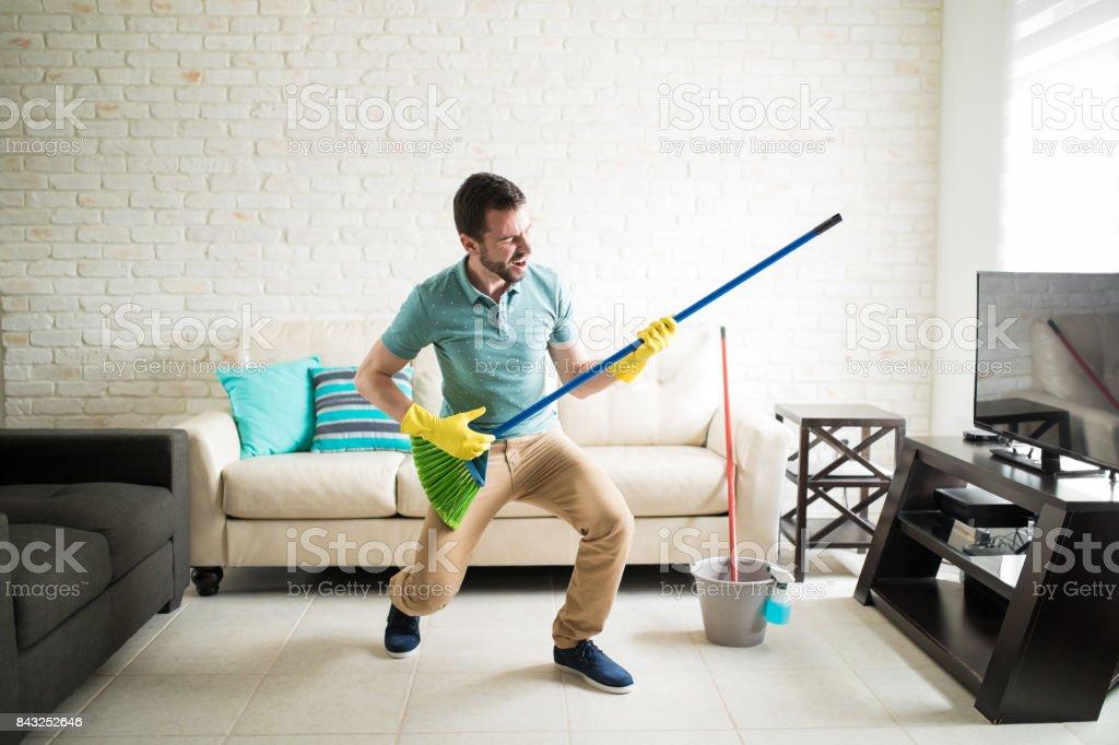Man having fun doing house chores stock photo