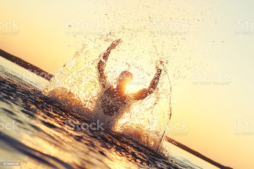 Man having fun in the water at sunset stock photo