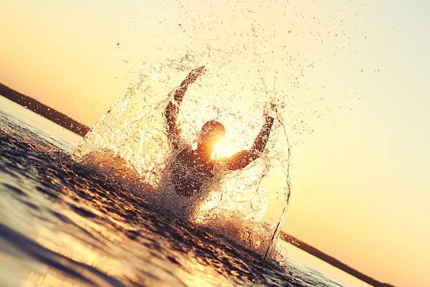 Man having fun in the water at sunset – Foto