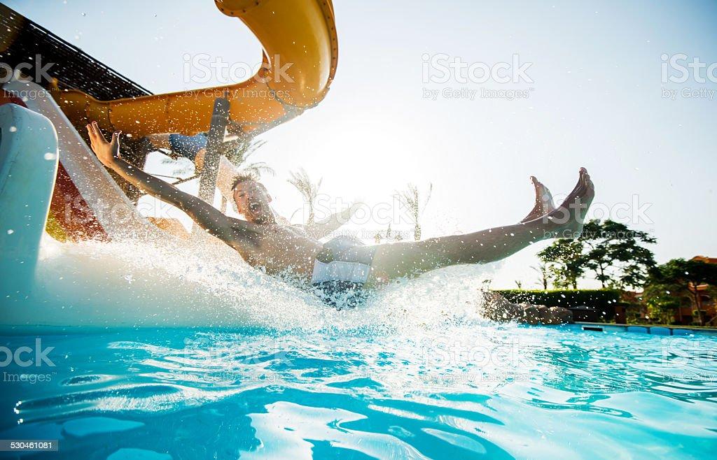 Man having fun on water slide. stock photo