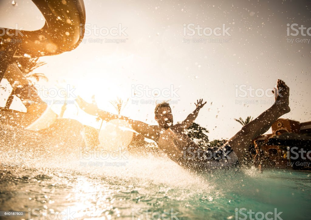 Man having fun while sliding into the swimming pool. stock photo