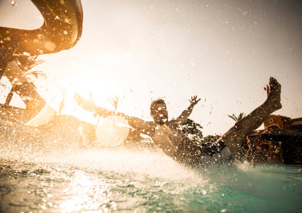 man having fun while sliding into the swimming pool. - sliding stock photos and pictures