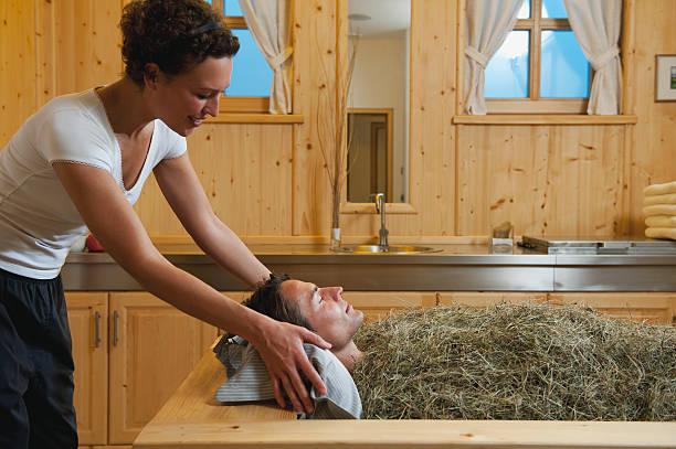 mann mit heu bad mit weiblicher therapeut - badewannenkissen stock-fotos und bilder