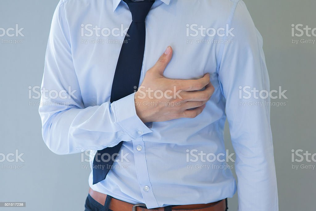 Man having heart-attack / chest pain in isolated background stock photo